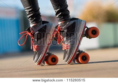 Close up of a young woman wearing rollerskates standing on toe during a bright sunny day. Legs of girl having roller skate exercise along road. Young woman on rollerskates on the road at summer time.