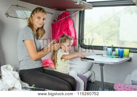 Young Mother Doing Her Hair Daughter On A Cot In A Train