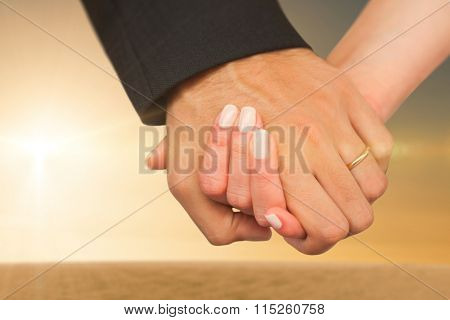 Newlyweds holding hands close up against desert scene