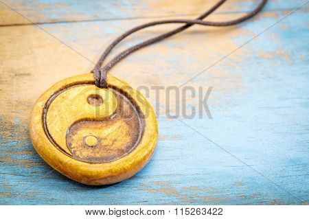 essential oil diffuser ceramic pendant with yin and yang symbol on grunge wood