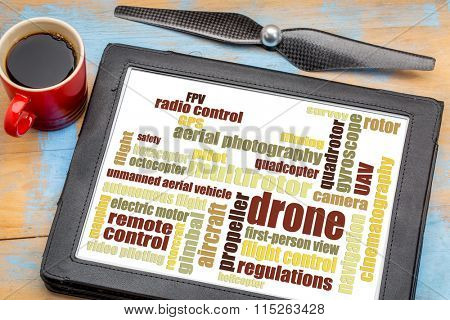 drone word cloud on a digital tablet with a cup of coffee and a drone propeller against a grunge painted wood
