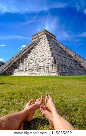 Pyramid Castillo In Chichen Itza And Relaxing Legs On Grass