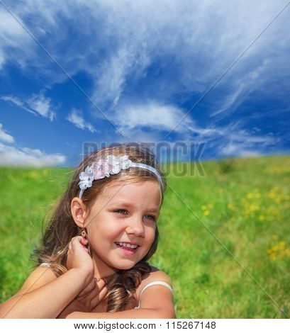 Smiling preschool girl sitting on a summer hill