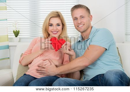 Happy Expecting Couple Holding Heart At Home