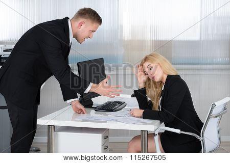 Boss Shouting At Employee Sitting At Desk