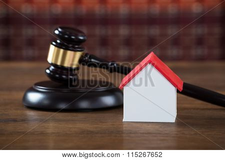 Mallet With House Model On Table In Courtroom