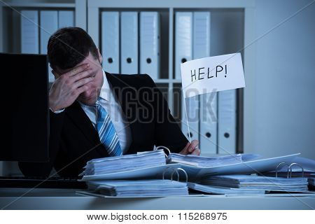 Stressed Accountant Holding Help Sign At Desk