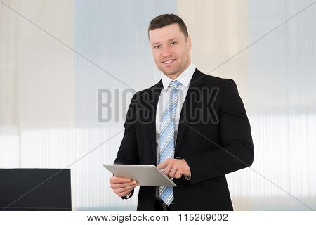 Businessman Using Digital Tablet In Office