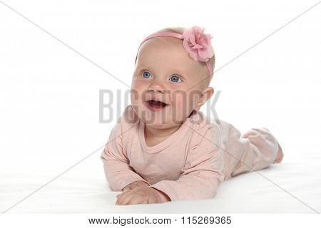 baby girl child lying down on white blanket smiling happy pink fashion portrait face studio shot isolated on white caucasian