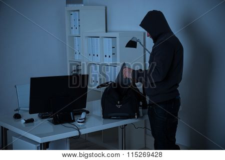 Burglar Putting Laptop Into Bag At Desk In Office