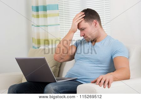 Upset Man With Laptop Sitting On Sofa