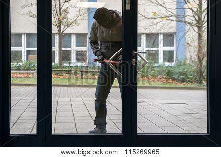 Hooded Man Using Crowbar To Open Glass Door