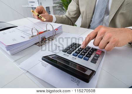 Accountant Using Calculator While Holding Magnifying Glass