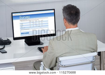 Businessman Filling Survey Form On Computer At Desk