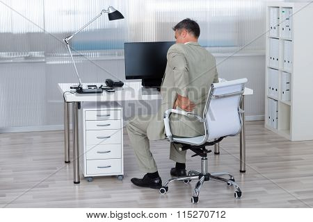 Businessman Suffering From Backache On Chair