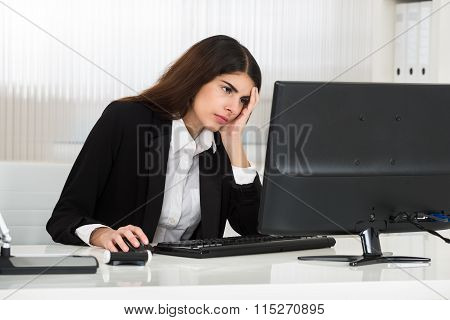 Stressed Young Businesswoman Using Computer At Desk