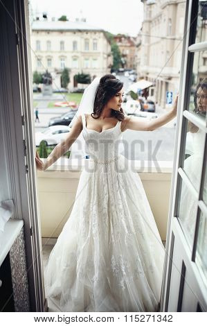 Gorgeous Brunette Bride In Sexy Wedding Dress Posing On Balcony City In The Background