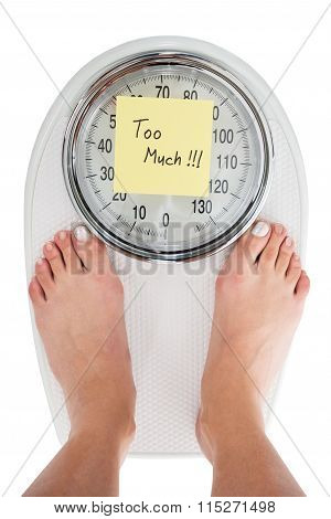 Woman Standing On Weight Scale With Too Much Note