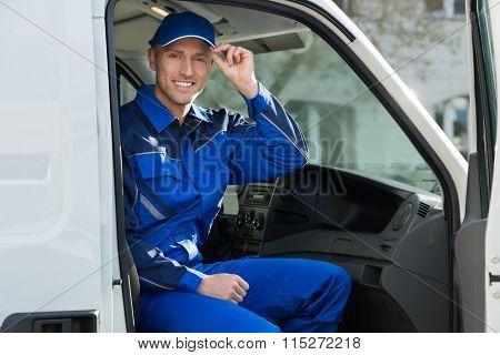 Portrait Of Happy Technician Sitting In Van