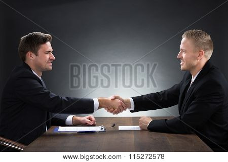 Young Businessmen Shaking Hands At Desk
