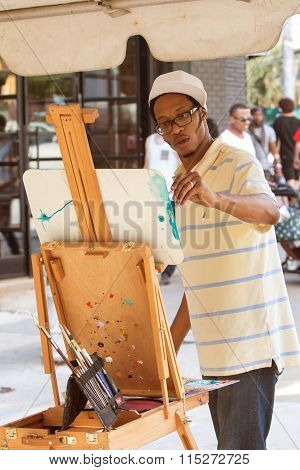 Artist Applies Brush Strokes To Painting At Arts Festival