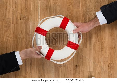 Businessmen Passing Lifebuoy Over Wooden Table
