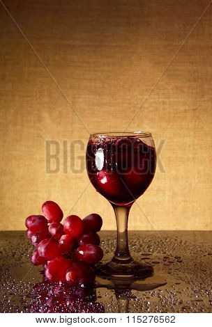 Glass Of Dry Wine And Red Grapes