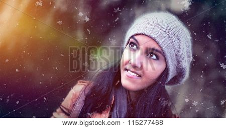 Attractive young Indian woman in a knitted winter hat watching the snow falling with a smile of pleasure and wonderment over a blurred outdoor background with copy space