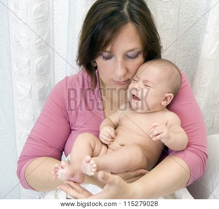 Mother with the crying baby on hands