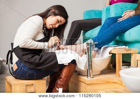 Applying Nail Polish On A Woman's Toes