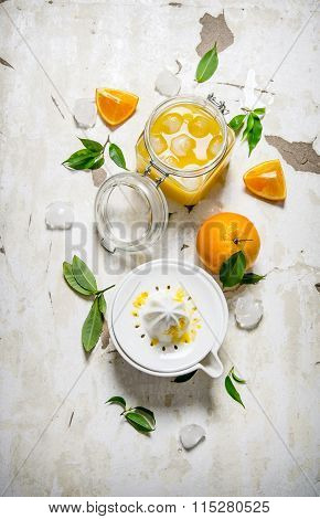 Fresh Orange Juice With Ice, With Slices Of Oranges And A Juicer.