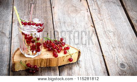 Cocktail Of Wild Currant With Ice On A Wooden Table. Free Space For Text.