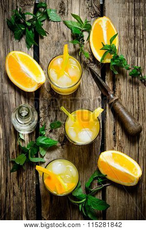Orange Cocktail With Vodka, Ice And Mint Leaves On A Wooden Table