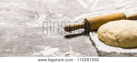 The Dough On The Paper With A Rolling Pin.