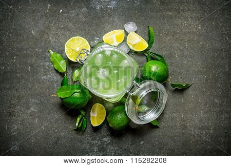 Lime Background. The Juice From The Limes With Ice And Sliced Limes Around .