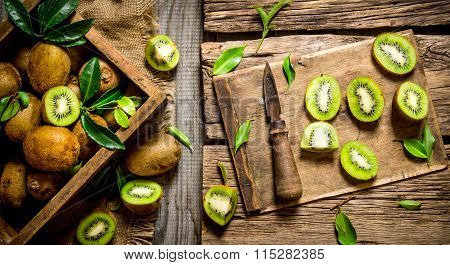 Sliced Kiwi On The Old Board With Knife And Box.