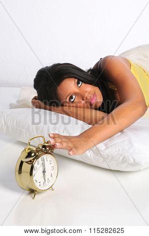 Young African American woman silencing alarm clock