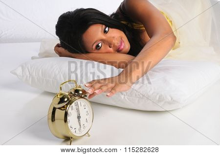 African American woman silencing alarm clock
