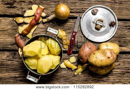 Peeled Potatoes In An Old Pan With Knife On Wooden Table .