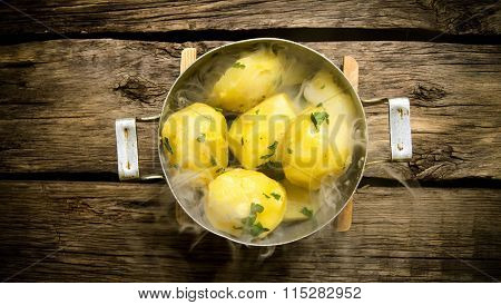 Boiled Potatoes With Herbs And Steam On A Wooden Table .