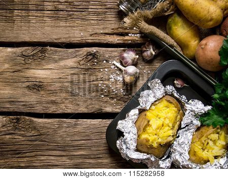 Baked Potatoes In Foil With Salt And Garlic On A Wooden Table . Free Space For Text.