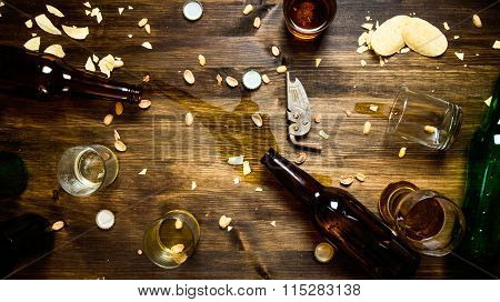 In The Process Of Party - Spilled Beer, Bottle Caps And Leftover Chips On The Table.