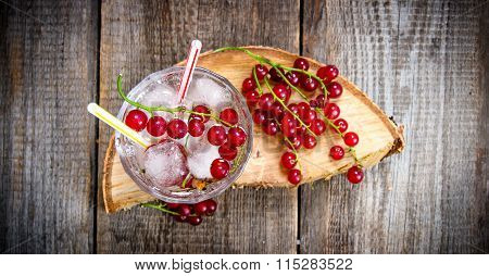 Cocktail Of Wild Currant With Ice On A Wooden Table.
