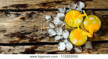 Three Cocktails From Fresh Oranges With Ice And Straw On Wooden Background . Free Space For Text.