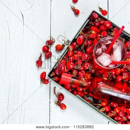 Cocktail With Rose Hip With Ice And Liquor On White Wooden Table .