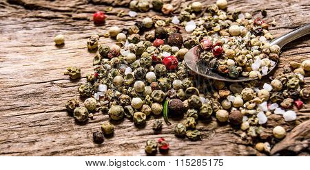 Spicy Peppercorns In A Spoon. On Wooden Background.