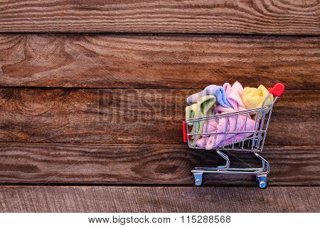 Shopping cart with clothing on the old wood background. Toned image.
