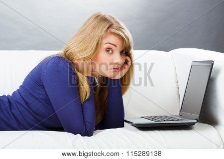 Sad Woman Lying On Sofa And Using Laptop, Modern Technology