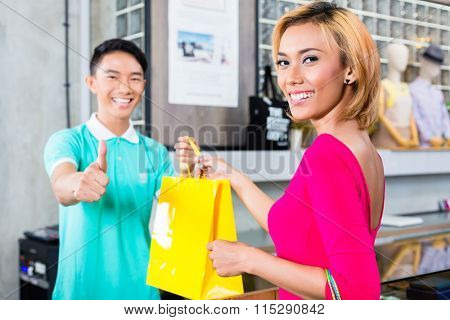Customer and shop assistant in Asian fashion store giving thumbs up