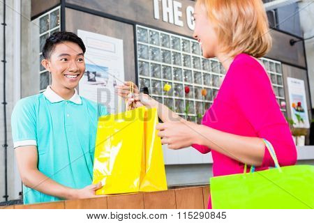 Shop assistant handing purchase in shopping bags to Asian woman